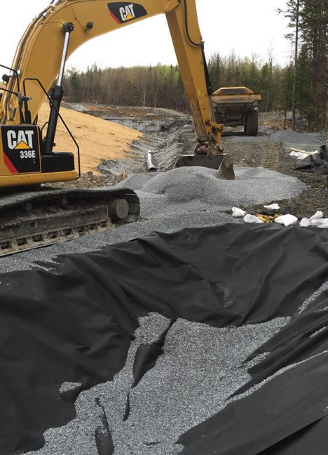 mechanical shovels installing crushed stone over nonwoven geotextile